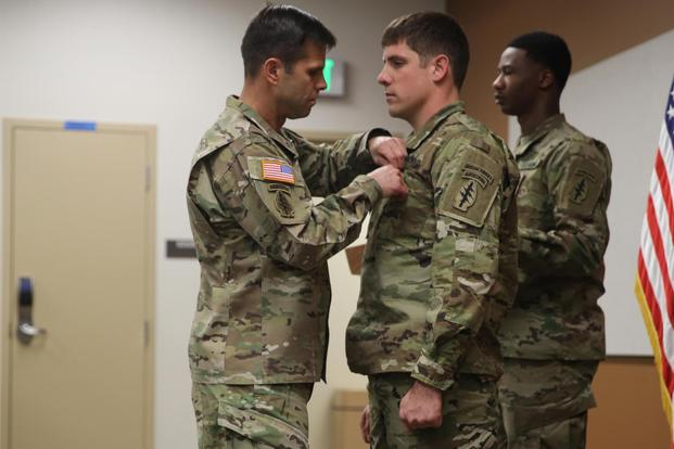 Brig. Gen. Richard Angle pins the Soldier's Medal on Staff Sgt. Adams, who is not being identified by his first name because of the nature of his job as a Special Forces soldier. (DEREK HAMILTON/U.S. ARMY)