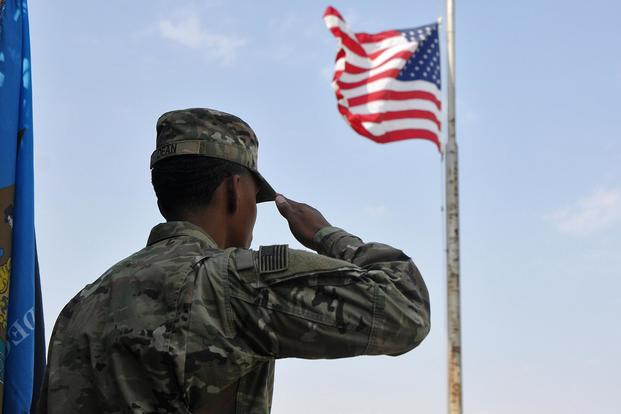 A soldier salutes the U.S. flag during the singing of the National Anthem on Sept. 11 2017 at Camp Arifjan Kuwait