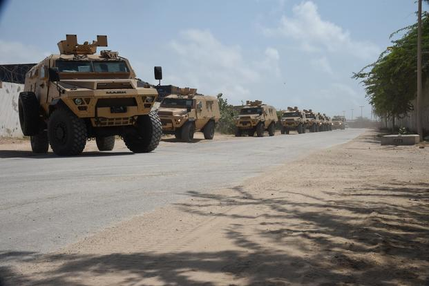 A convoy of armored troop carrying vehicles provided by the U.S. Department of Defense and Department of State drive to the Uganda People's Defence Force compound, Mogadishu International Airport, Somalia, Sept. 25, 2017. (U.S. Air National Guard/Tech. Sgt. Andria Allmond)