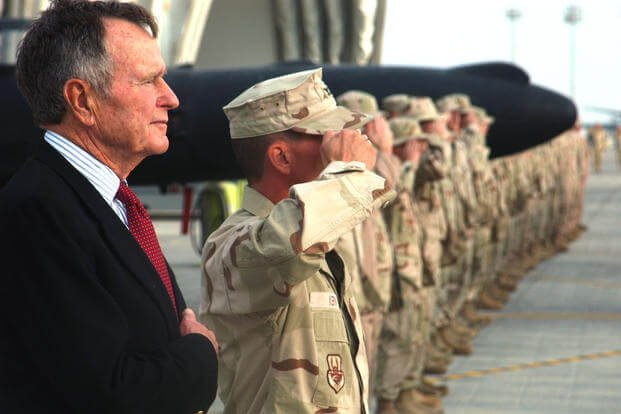 Former President George H.W. Bush listens to the national anthem with Airmen from the 380th Air Expeditionary Wing in 2006