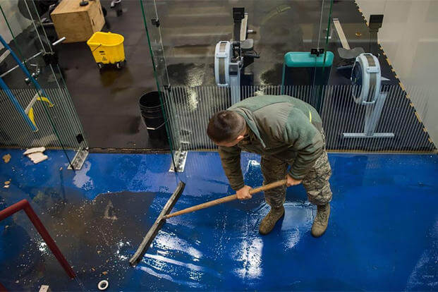 An airman at Joint Base Elemendorf Richardson sweeps water at the base's Buckner Fitness Center a day after a 7.0 earthquake rattled the region