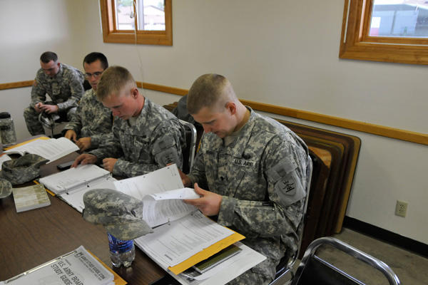 Soldiers studying at a desk.
