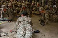 U.S. Army Drill Sgt. Angela Lee, who is with the 98th Training Division (IET), does pushups with her platoon during white phase of basic combat training at Fort Jackson, S.C., March 14, 2015. (U.S. Army photo by Sgt. Ken Scar)