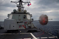 The destroyer USS Mustin fires its 5-inch gun during a live fire exercise in waters off Japan in January 2015. Last week, the warship sailed near disputed territory claimed by China. (US Navy photo/Christian Senyk)