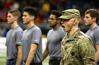 An Army soldier marches recruits onto the football field at the Alamodome in San Antonio, Texas, on Jan. 6. The Army has lowered its recruitment goal for this year to 76,500 new troops. (US Army photo/Ian Valley)