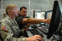 Capt. Eva Kelly, 38th Sustainment Brigade, receives instruction from Tony Torres on a tactical battle command system in a tactical operation center setup at Grissom Air Reserve Base, Indiana. (U.S. Army/William E. Henry)