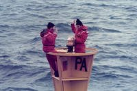 "Chief Petty Officer Bob Trainor reenlists on ""PA"" Lighted Buoy in the Straits of Juan de Fuca, while stationed aboard Coast Guard Cutter Fir (WLM-212) in February 1986. (Photo courtesy of Bob Trainor)"