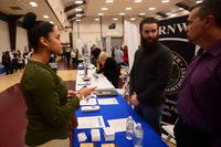 Personnel Specialist 2nd Class Kendra Velasquez from Syracuse, N.Y., Speaks with representatives from Commander Navy Region Northwest during a job fair. (U.S. Navy/Christopher R. Jahnke)