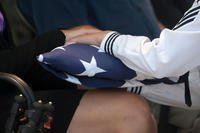 Danielle Myers, the great niece of U.S. Navy Machinist's Mate 1st Class Arthur Glenn, receives an American flag during a funeral at the National Memorial Cemetery of the Pacific, Honolulu, Hawaii, Aug. 21, 2018. On Dec. 7, 1941, Glenn was assigned to the USS Oklahoma which sustained fire from Japanese aircraft. (U.S. Navy/Seth Coulter)