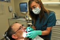 dental assistant examines patient