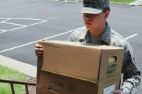 A servicemember carrying a box