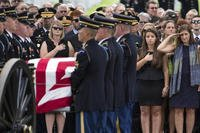 Retired Col. Susan Myers, right, stands with her daughter Amelia Greene and salutes as the casket of her husband, Army Maj. Gen. Harold Greene, is carried by an honor guard during a burial service at, in Arlington, Va. (AP Photo/Evan Vucci)