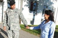 Servicemember and wife holding hands.
