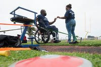Shundra Johnson returns a wedding ring to her husband Coast Guard Lt. Sancho Johnson after his seated discus practice Navy's wounded warrior training camp. Shundra is also her husband's caregiver. (DoD News photo by EJ Hersom)